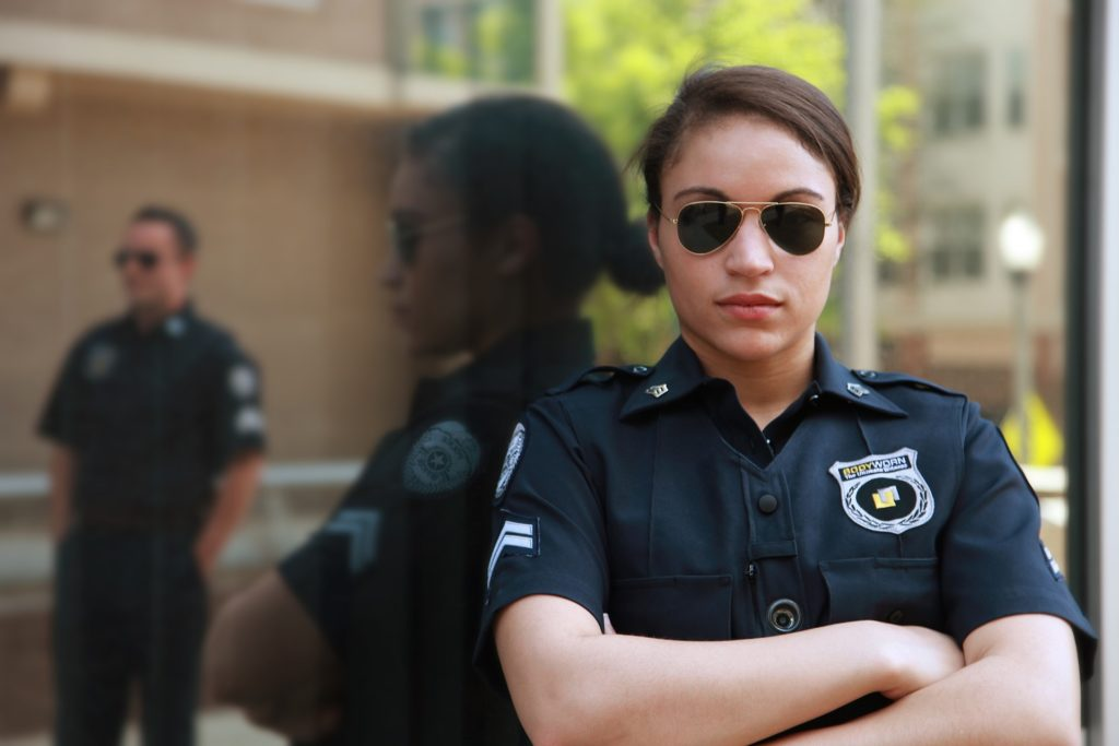 A woman wearing a security guard uniform and sunglasses with crossed arms.